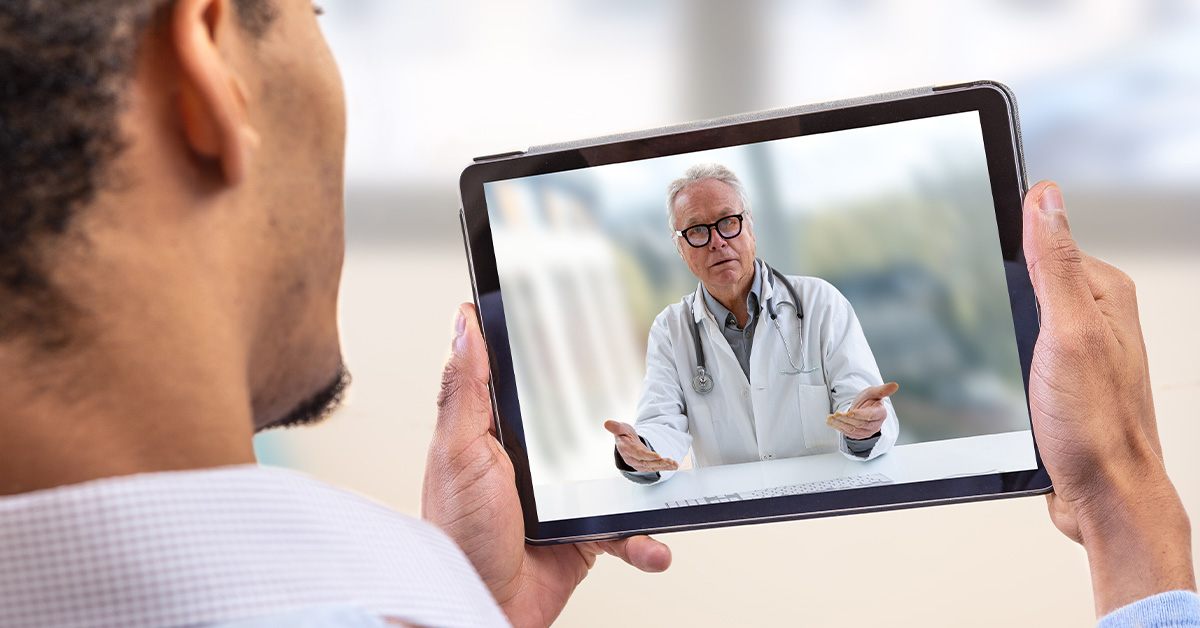 Telemedicine Image, man holding tablet while on a call with a doctor.